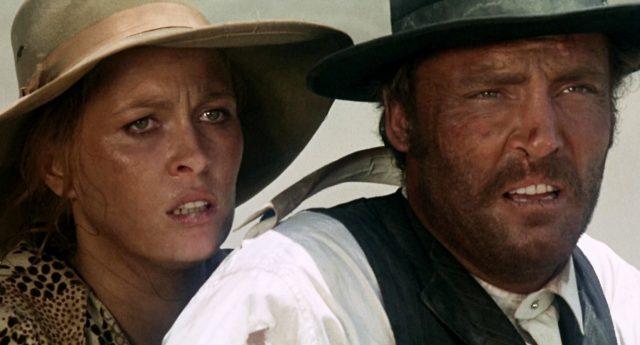 Nahaufnahme von Faye Dunaway als Katie Elder und Stacy Keach als Doc Holliday beim Ritt durch die Wüste