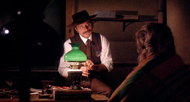Wyatt Earp (gespielt von Harris Yulin) sitzt neben einer Tischlampe auf einem Schreibtisch, Copyright: Frank Perry Films, Black Hill Pictures