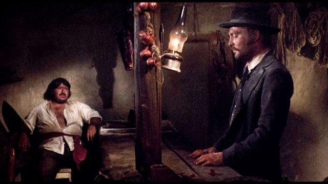 links sitzt der mexikanische Barkeeper (gespielt von Marshall Efron) in einer Ecke hinter dem Tresen, während Doc Holliday (gespielt von Stacy Keach) rechts am Tresen steht, Copyright: Frank Perry Films, Black Hill Pictures