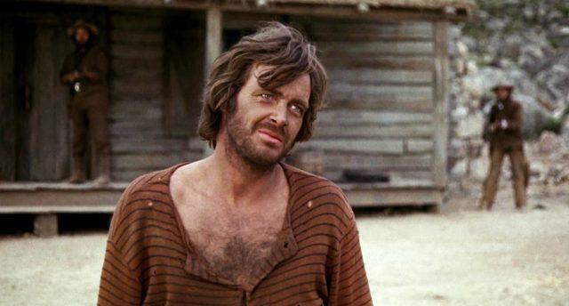 Ike Clanton (gespielt von Michael Witney) steht mit weitem Brusthaarausschnitt vor seinem Haus