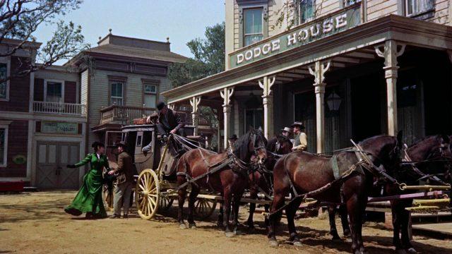 Kutsche parkt vor einem Hotel, während eine Frau aussteigt