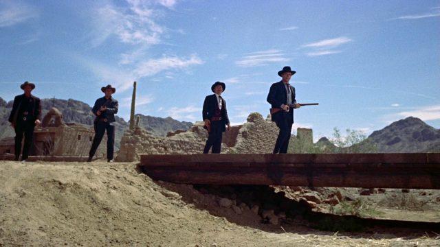 Doc Holliday und die Earp-Brüder schreiten über eine flache Holzbrücke zum Duell mit der Clanton-Gang