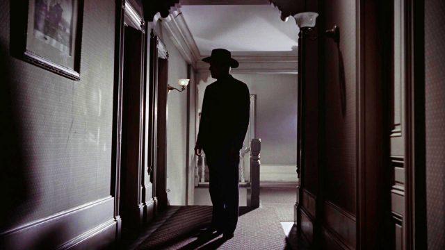 ins Dunkel getauchter Körper vor der Tür eines Hotelzimmers
