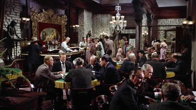 vollbesetzter Saloon mit mehreren Tischen und der Bar