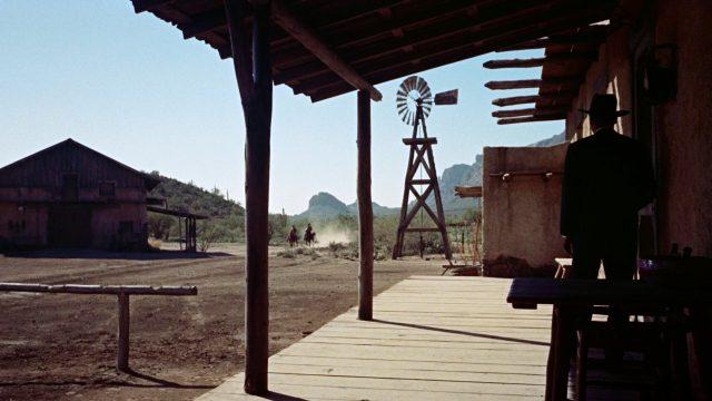 ein ins Dunkel getauchter Mann steht auf der Veranda einer Ranch und blickt zwei herannahenden Reitern entgegen; im Hintergrund dreht ein hohes Windrad