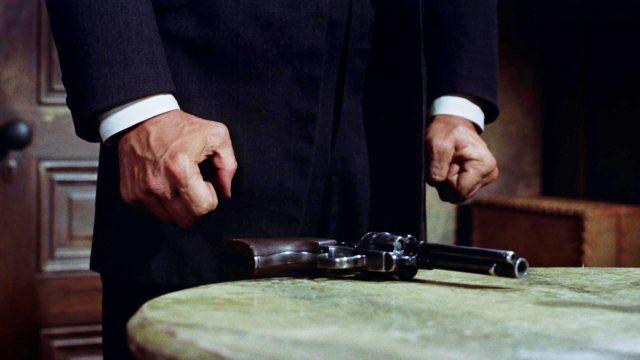 zwei angespannte Fäuste vor einem Tisch, auf dem ein Revolver liegt