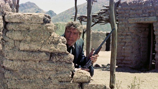 Burt Lancaster als Wyatt Earp mit Gewehr hinter einer Mauer verschanzt