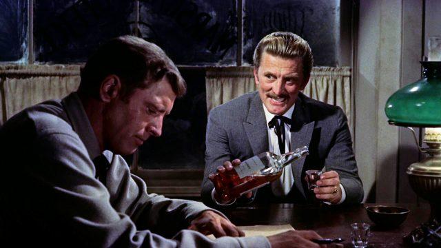Doc Holliday (gespielt von Kirk Douglas) gießt sich am Tisch Whiskey ein, während neben ihm Wyatt Earp (gespielt von Burt Lancaster) mit konzentriertem Blick auf ein Blatt Papier sitzt, Copyright: Paramount, HalB. Wallis & JosephH. Hazen
