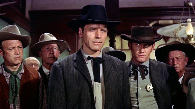 Wyatt Earp (gespielt von Burt Lancaster) steht im Raum eines Gebäudes, hinter im steht eine Reihe Männer