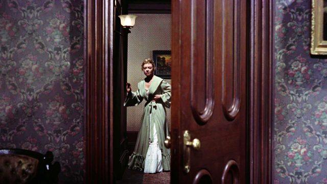 Kate Fisher (gespielt von Jo Van Fleet) steht im Gang des Hotels und blickt in die offene Tür von Doc Hollidays Zimmer