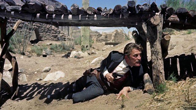 Doc Holliday (gespielt von Kirk Douglas) liegt mit gezücktem Revolver unter einer Brücke in Deckung
