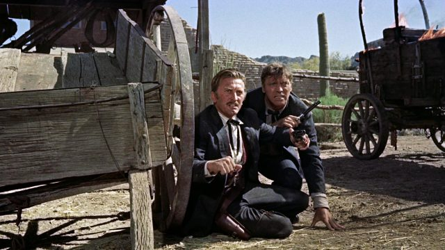 Doc Holliday (gespielt von Kirk Douglas) und Wyatt Earp (gespielt von Burt Lancaster) sind während der Schießerei am O.K. Corral am Rad eine Kutsche in Deckung gegangen