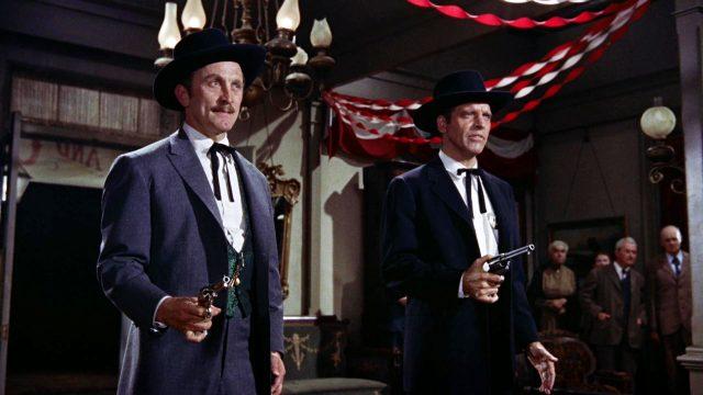 Doc Holliday (gespielt von Kirk Douglas) und Wyatt Earp (gespielt von Burt Lancaster) stehen mit gezückten Revolvern in einem Saloon, Copyright: Paramount, HalB. Wallis & JosephH. Hazen
