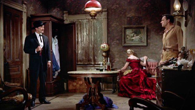 Konfrontation zwischen Doc Holliday (gespielt von Kirk Douglas) und Johnny Ringo (gespielt von John Ireland) im Hotelzimmer; im Hintergrund sitzt Kate Fisher (gespielt von Jo Van Fleet) mit abgewandtem Gesicht, Copyright: Paramount, HalB. Wallis & JosephH. Hazen