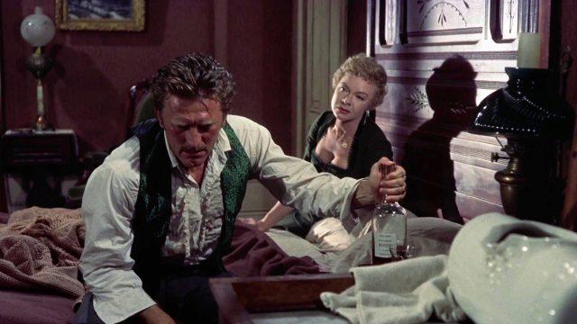 Doc Holliday (gespielt von Kirk Douglas) sitzt mit gesenktem Kopf auf dem Bett seines Hotelzimmers und hält am ausgestreckten Arm eine Whiskey-Flasche fest; im Hintergrund beugt sich Kate Fisher (gespielt von Jo Van Fleet) zu ihm vor, Copyright: Paramount, HalB. Wallis & JosephH. Hazen