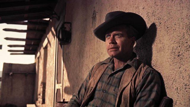 Ike Clanton (gespielt von Lyle Bettger) sitzt bei schwachem Licht auf der Veranda seiner Ranch