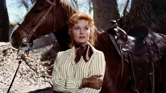 Rhonda Fleming als Laura Denbow, die auf einem bewaldeten Flecken vor ihrem Pferd steht