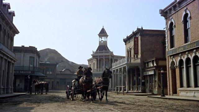 """eine Pferdekutsche fährt durch Tombstone, auf der rechten Seite befindet sich ein Gebäude mit der Aufschrift """"Turnverein"""""""