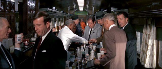 männliche Fahrgäste tummeln sich im Zug an der Bar