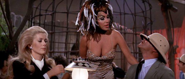 Catherine Gunther (gespielt von Catherine Deneuve) und Howard Brubaker (gespielt von Jack Lemmon) sitzen am Tisch in einem exzentrischen Nachtclub, zwischen ihnen eine Bedienung in exotischem Outfit; Brubakers Tropenhut ist ihm ins Gesicht gerutscht