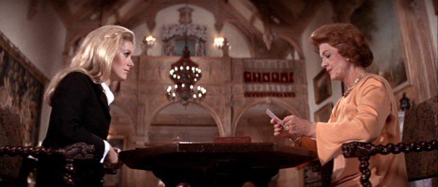 Catherine Gunther (gespielt von Catherine Deneuve) sitzt am Tisch mit der Karten legenden Grace Greenlaw (gespielt von Myrna Loy) im stattlichen Anwesen der Greenlaws