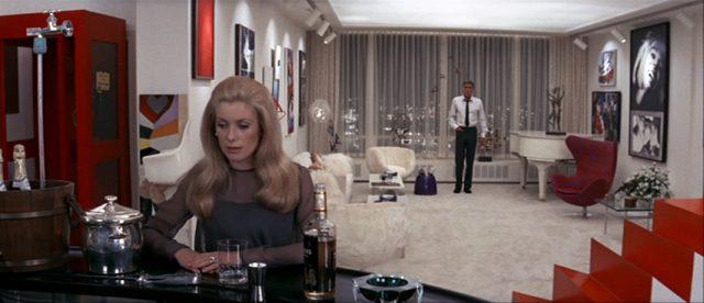 Catherine Gunther (gespielt von Catherine Deneuve) steht an der Bar in ihrem Appartement, im Hintergrund steht Ted Gunther (gespielt von Peter Lawford)