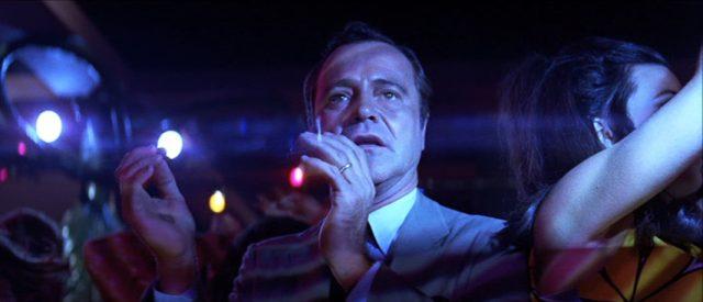 Jack Lemmon, in blaues Discolicht getaucht, als Howard Brubaker