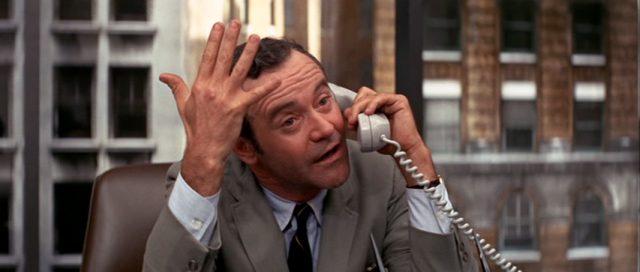 Howard Brubaker (gespielt von Jack Lemmon) gestikulierend am Telefon in seinem Büro
