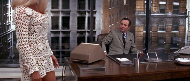 Howard Brubaker (gespielt von Jack Lemmon) sitzt im Büro an seinem Schreibtisch, seiner Sekretärin zugewandt