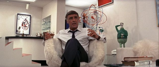 Ted Gunther (gespielt von Peter Lawford) sitzt mit Whiskey-Glas und Zigarette in seinem Appartement