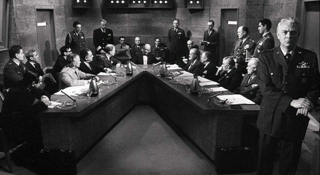 Frontalaufnahme eines V-förmigen Konferenztisches, an dem Politiker, Militärs und Berater zusammengekommen sind