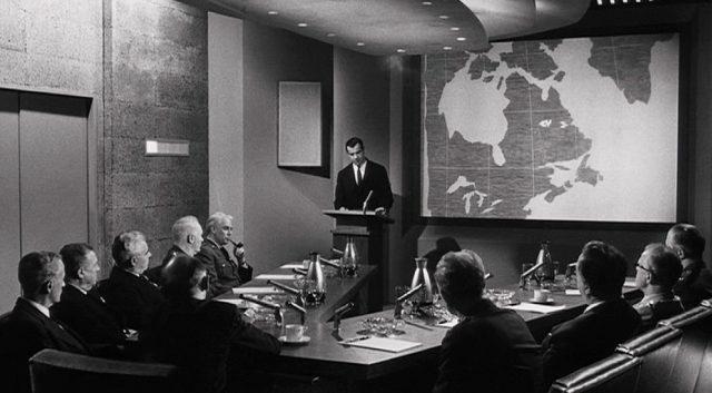 Groeteschele steht am Rednerpult vor einer großen Karte, im Vordergrund ein voll besetzter v-förmiger Konferenztisch