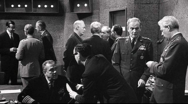 Blick in eine der Entscheidungszentralen, in denen sich mehrere Männer in kleinen Gruppen unterhalten