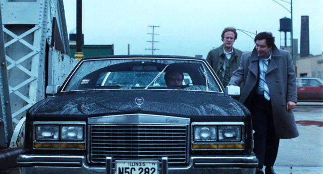 Frank (gespielt von James Caan) wartet in verregneter Umgebung in seinem Cadillac, während sich von hinten zwei Cops dem Fahrzeug nähern, Copyright: MGM
