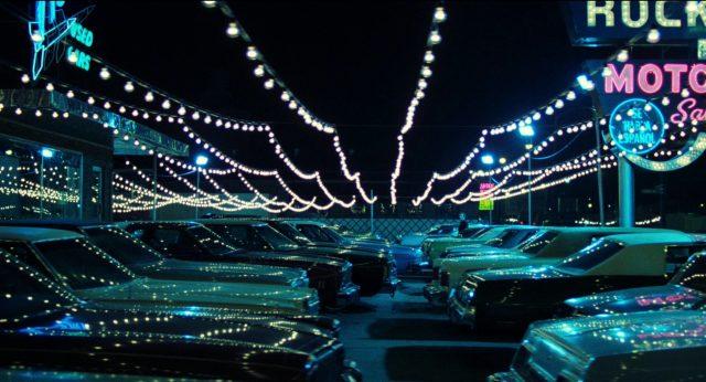 Frank nachts auf dem von zahlreichen kleinen Lichtern erleuchteten Parkplatzes seines Gebrauchtwagenhandels