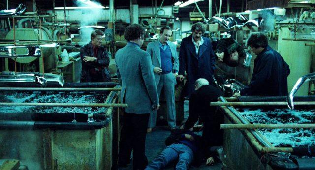 eine Gruppe Gangster in einer Fabrikhalle