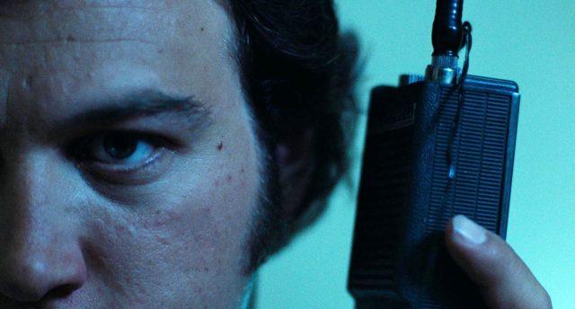 Nahaufnahme einer Gesichtshälfte von Barry (gespielt von James Belushi), der ein Funkgerät an sein Ohr hält