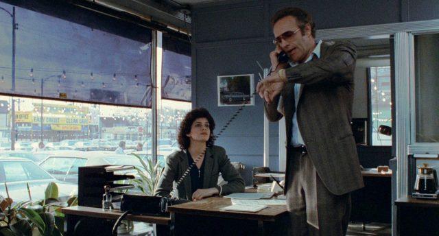 Frank (gespielt von James Caan) steht mit aufgesetzter Sonnenbrille in seinem Autohandelsbüro und telefoniert, am Schreibtisch sitzt eine Sekretärin, Copyright: MGM