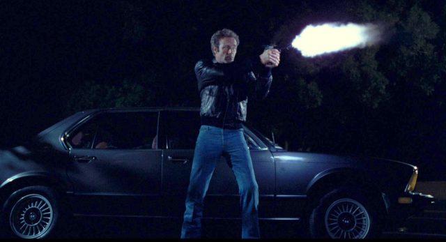 Frank (gespielt von James Caan) steht nachts vor einem quer geparkten Fahrzeug und feuert seine Waffe ab