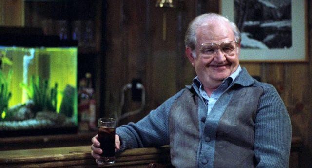 Leo (gespielt von Robert Prosky) sitzt lachend mit einem Getränk an den Tresen einer Bar