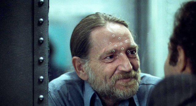 Okla (gespielt von Willie Nelson) unterhält sich im Gefängnis durch die Sicherheitsscheibe