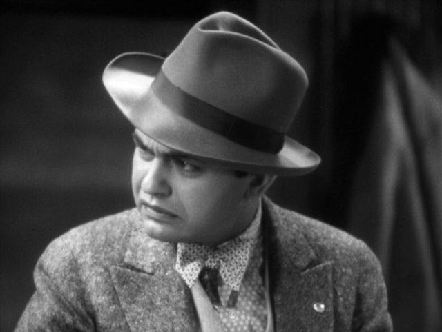 Edward G. Robinson blickt als Caesar Enrico Bandello in Gangstermontur bedrohlich zur Seite.