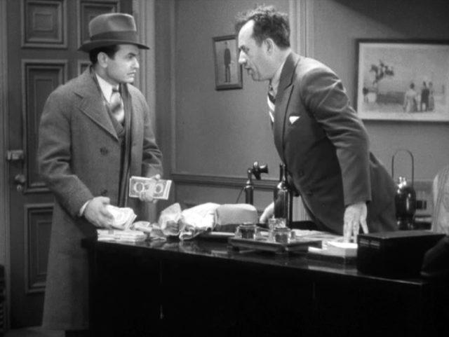 Bandello (gespielt von Edward G. Robinson) drapiert mit finsterem Blick Geldbündel auf dem Schreibtisch seines aufgebrachten Bosses (gespielt von Stanley Fields).