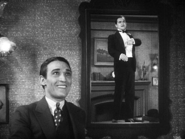 Otero (gespielt von George E. Stone) bewundert lachend seinen Boss Bandello (gespielt von Edward G. Robinson), der im Spiegel in eitler Pose zu sehen ist.