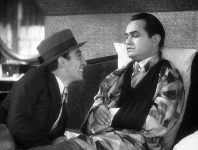 Otero (gespielt von George E. Stone) lehnt sich grinsend zu Bandello (gespielt von Edward G. Robinson) herüber; Letzterer liegt mit einer dunklen Armbinde in seinem Bett., Copyright: Turner Entertainment