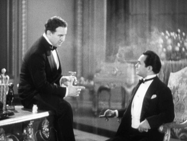 """der """"Big Boy"""" genannte Oberboss (gespielt von Sidney Blackmer) sitzt an der Kante seines barocken Schreibtisches, im Gespräch mit Bandello (gespielt von Edward G. Robinson), der ihm gegenüber mit Zigarre in einem Sessel sitzt."""