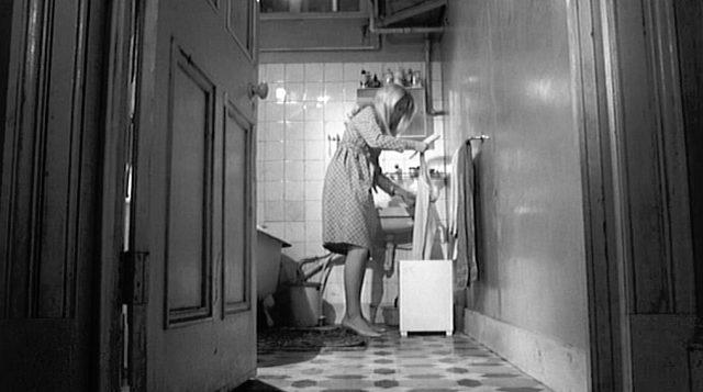 Carol (gespielt von Catherine Deneuve) steht bei offener Tür am Waschbecken im Badezimmer ihres Appartements