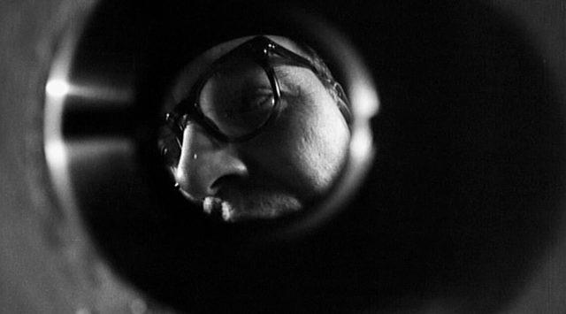 skurrile Perspektive durch den Türspion, in dem ein Mann mit Hornbrille zu erkennen ist
