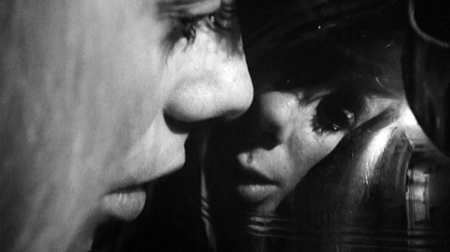 bizarre Nahaufname von Carol Ledoux (gespielt von Catherine Deneuve) mit Spiegelbild