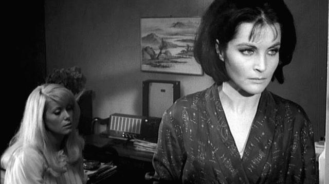 Carol (gespielt von Catherine Deneuve) sitzt im Hintergrund auf dem Bett, im Vordergrund steht, zur rechten Bildseite blickend, ihre Helen (gespielt von Yvonne Furneaux)